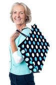 Old woman carrying shopping bag — Stockfoto