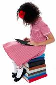 Girl sitting on books with digital tablet — Stock Photo