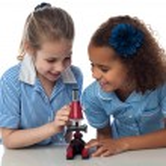Little school girls working with microscope — Stock Photo #81621574