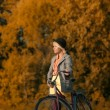 Pretty girl go for a bike ride in the autumn forest — Stock Photo #54983287