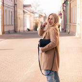 Amazing blonde girl walking alone on the road in old european city. — Stockfoto