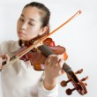 Beautiful young woman playing violin over white background — Stock Photo #64726985