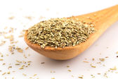 Dried rosemary leaves in wooden spoon — Stock Photo