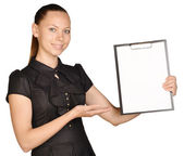 Beautiful girl holding a clipboard in hand and showing blank white paper. — Stock Photo