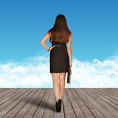 The girl goes on the boards to blue clouds — Stockfoto
