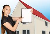 The girl on background of house holding clip board pointing forefinger — Stock Photo