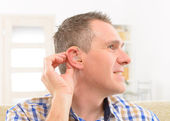Man showing deaf aids — Stock Photo