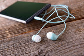 Small headphones with mobile phone — Stockfoto