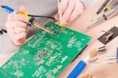 Serviceman soldering on PCB — Stock Photo