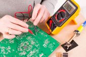 Serviceman checks PCB with a digital multimeter — Stock Photo