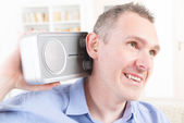 Hearing impaired man trying to listen radio — Stock Photo