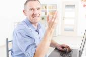 Hearing impaired man working with laptop — Stock Photo