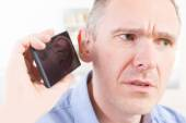 Hearing impaired man using mobile phone — Stock Photo