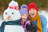 Father and daughter with snowman — Stock Photo