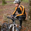 Cyclist resting on a bench in nature — Stock Photo #59728643