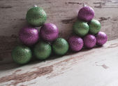 Pink and green christmas balls in a stack over wooden background — Stock Photo