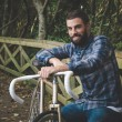 Hipster man with a fixie bike and smiling — Stock Photo #59734567