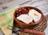 Eggs with french fries and small sausages — Stock Photo