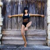 Dancer with a black leotard against a wooden door. — Stock Photo