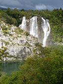 Vredige landschap met waterval groen water, rotsen, bomen. — Stockfoto