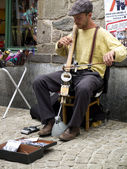 Anonymous street musician playing stringed instrument. — Stock Photo