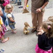 Children looking at a wooden puppet in the street. — Stock Photo