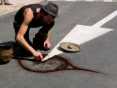 Street performer draw a symbol on the asphalt. — Stock Photo