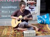 Barefoot and hairy musician playing the guitar in the street. — Stok fotoğraf
