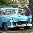 Old man cleaning his vintage american blue car in Havana. — Stock fotografie #64779755