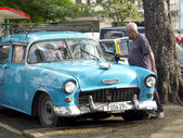 Old man cleaning his vintage american blue car in Havana. — Stockfoto