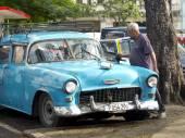 Old man cleaning his vintage american blue car in Havana. — Foto de Stock