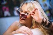 Fröhlich, modische Blondine mit Sonnenbrille — Stockfoto