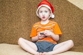 Boy using his smartphone while seated in front of the Christmas tree. — Stock fotografie