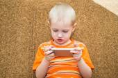 Little boy sitting on the couch playing in the smartphone — Stock Photo