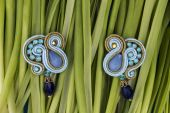 Soutache bijouterie blue earrings with blue stones and light-blue and cyan crystals on the green background of grass stems — Stock Photo