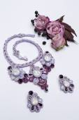 Soutache bijouterie set purple earrings and necklaces with white purple and pink crystals on white background with small roses black berries and dark red leaves — Stock Photo