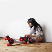 Woman putting roller-skates — Stock Photo