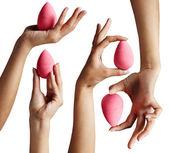 Hands holding makeup sponges — Stock Photo