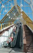 Bogdan Khmelnitsky (Kievsky) Pedestrian Bridge (2001), passers-by on escalator — Stock Photo