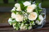 Wedding bouquet of cream roses and green leaves on wooden bench — Stock Photo