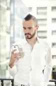 Modern man using a smartphone in the city — Stock Photo