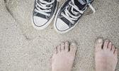 Flickans fötter och sneakers på sanden på stranden, sommartid — Stockfoto