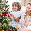 Mother and children decorating Christmas tree — Stock Photo #53897149