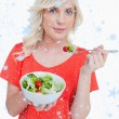 Young blonde woman eating a vegetable salad — Stock Photo #53897261