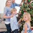 Family decorating Christmas tree — Stock Photo #53899031