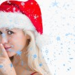 Composite image of woman in santa hat making silence gesture — Stock Photo #53899493