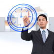 Serious asian businessman pointing to clock — Stock Photo #53899823