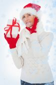 Composite image of festive woman listening and holding gift — ストック写真