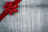Composite image of red christmas bow and ribbon — Stock Photo