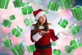 Composite image of pretty girl in santa costume holding hand out — Photo